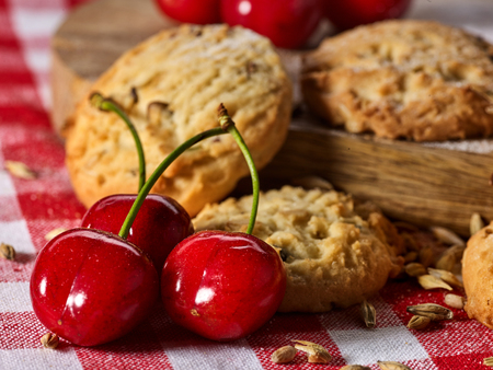 Oatmeal cookies with husk oats and cherry on kitchen cutting board gingham checkered cotton fabric on table in village style for picnic close up.