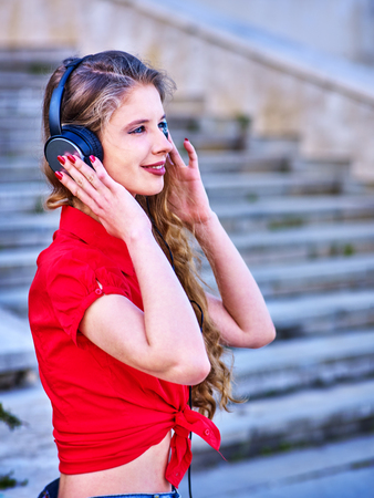 Girl in headphones listens to music and walking down stairs in city.