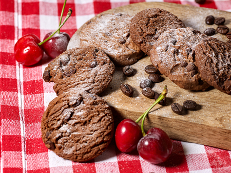 Oatmeal chocolate cookies with coffee grains and cherry, powdered sugar on kitchen cutting board with checkered fabric on wooden table in village style for picnic. Limitations for diabetics.