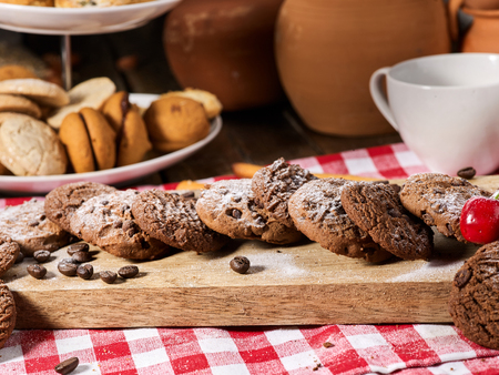 Oatmeal chocolate cookies with coffee grains and cherry, powdered sugar on kitchen cutting board with checkered fabric in village style for picnic. Easily digestible and quickly digestible substances.