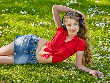 Girl in headphones and mini denim skirt catch rhythm music on green grass with chamomile flowers summer outdoor.