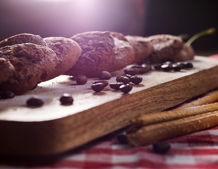 Oatmeal chocolate cookies with coffee grains and cherry , powdered sugar on kitchen cutting board on wooden table in village style for picnic. Sun flare in morning sunrays tone image. Perfect product.