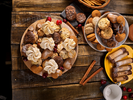 Oatmeal cookies and sand chocolate cake with cherry berry and crispy wafer rolls with cream on cutting board on wooden table in rustic style. Limitations for diabetics. Delicatessen products.