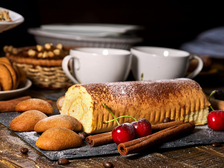 Oatmeal cookies and rolled cake on tier cake stand with cherry and nut on kitchen on wooden table in village style. Two cups of tea on wooden table. Delight pleasant taste. Limitations for diabetics.