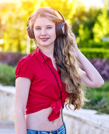 Girl in headphones and denim listens to music with closed eyes and sidewalk walking in city alone. Active participation in social events.