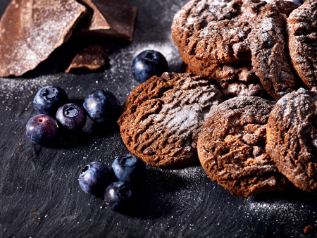 Serving food on slate onto wooden table. Oatmeal cookies biscuit with blueberry on picnic dark tiles countrylike. Chocolate chip cookies tied with string. Dessert in cafe. 스톡 콘텐츠