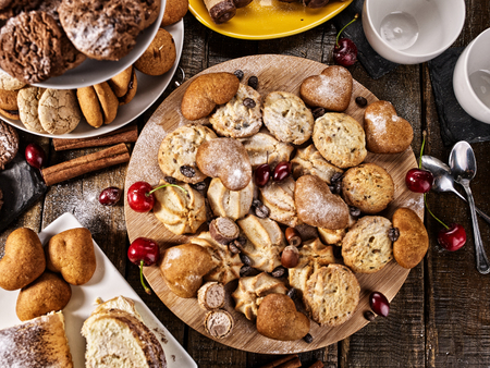 Oatmeal cookies and sand chocolate cake with cherry berry and crispy wafer rolls with cream on cutting board on wooden table in rustic style. Limitations for diabetics. Traditional sweets. Reklamní fotografie