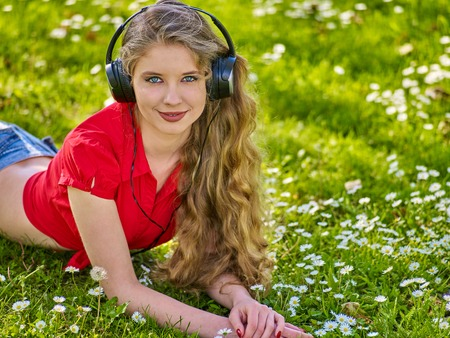 Girl in headphones catch rhythm music on green grass with chamomile flowers summer outdoor. Walking reduces risk of developing depression.