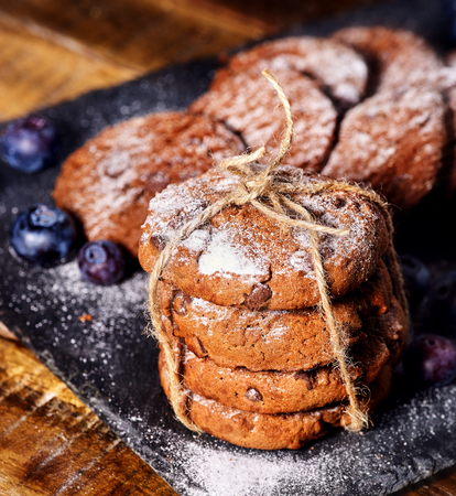 Serving food on slate onto wooden table. Oatmeal cookies biscuit with blueberry on picnic dark tiles countrylike. Chocolate chip cookies tied with string. Chemical-free sweet foods.