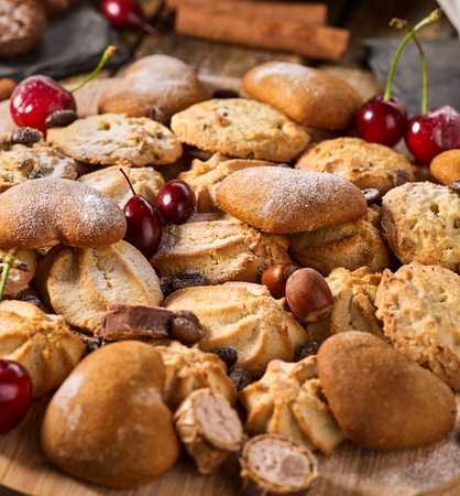 Oatmeal Cookies and sand chocolate cake with nut on wooden table in farm style close up. Easily digestible and quickly digestible substances.