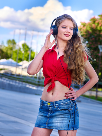 Girl in headphones listens to music in city