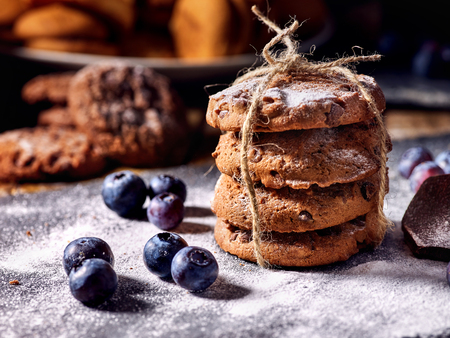 Bakers gonna bake. Serving food on slate. Oatmeal cookies biscuit with blueberry on dark tiles countrylike. Chocolate chip cookies tied with string shop on window display. Confectionery production. Stock Photo