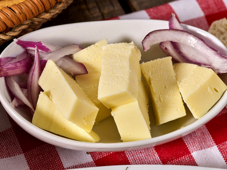 Cheese with onion on plate and checkered napkin in village style.