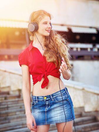 Girl in headphones listens to music and walking down stairs in city 版權商用圖片