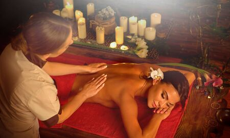 Masseuse give a massage to woman in spa salon with candles and sun flare.