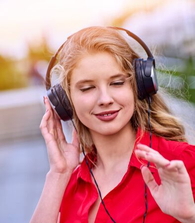 Student girl in headphone listen music after exam. Time to relaxin street city. Walking improves memory and concentration.
