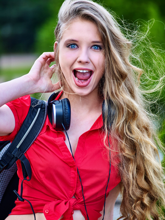 Student girl with backpack in headphone listen music after exam. Surprised girl face.