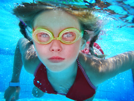 Girl in goggles swim and dive under water. Portrait of kids face and body float in pool.