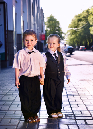 Children in business suits in center outdoor city street. Concept of boy and girl in smart suit hold hands.