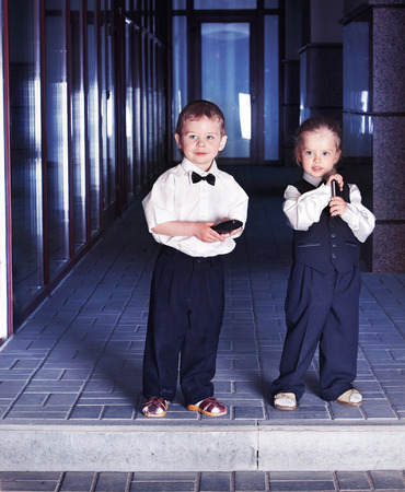 Children in business suits in center outdoor city street. Concept of boy and girl in smart suit take loan for education in bank.