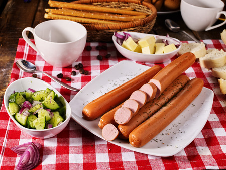 Sausage portion with bread baguette on table setting on checkered tablecloth and cup in farm style. How and from what make sausages. Imagens