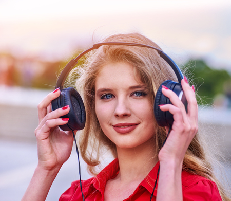 Student girl in headphone listen music after exam. Time to relaxing street city. Walking reduces risk of developing depression.