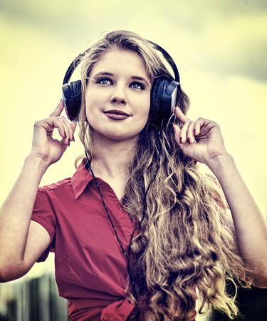 Student girl in headphone listen music after exam. Time to relaxin street city sepia tone image . 版權商用圖片