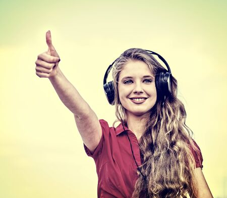 Student girl in headphone listen music after exam and show thumb up. Time to relaxin street city sepia tone image . 版權商用圖片