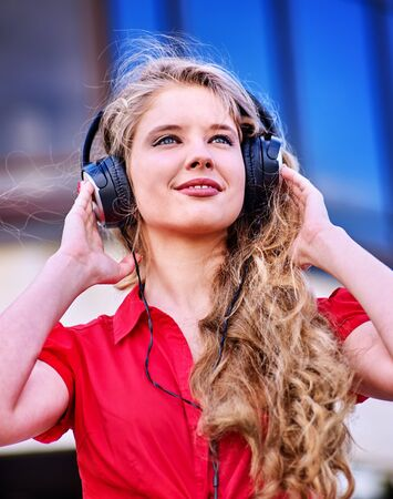 Student girl in headphone listen music after exam. Time to relaxin street city near high building.