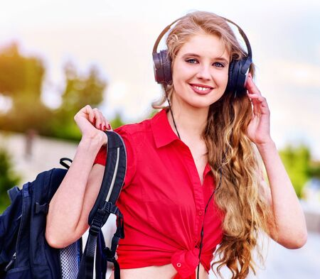 Student girl with backpack in headphone listen music after exam. Time to relaxin street city.