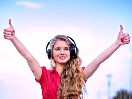 Student girl in headphone listen music and show thumb up after exam. Time to relaxin street city. 版權商用圖片