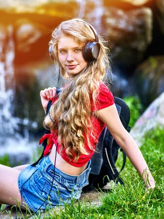 Student girl with backpack in headphone listen music after exam. Time to relaxing on green grass near waterfall nature.
