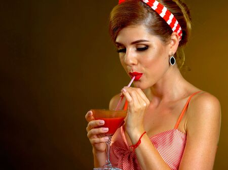 Woman in retro style drinks bloody Mary cocktail of martinis glass on theme party Stock Photo