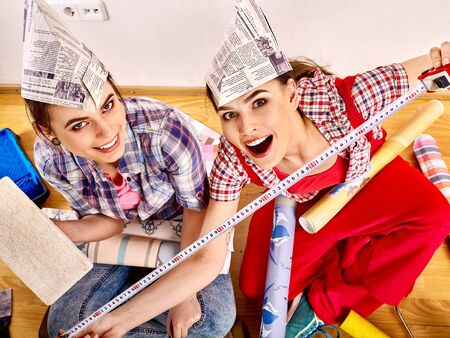 Women make repairs in apartment and hang wallpaper.