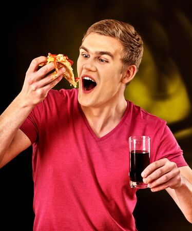 Man eat fast food pizza piece and drink glass of cola with good appetite.