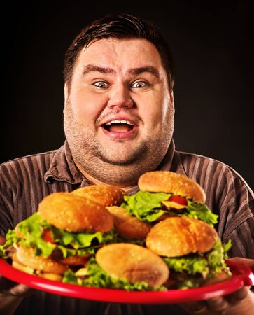 Fat man eats burgers. Obeseness and gluttony of fast food hamburger concept.