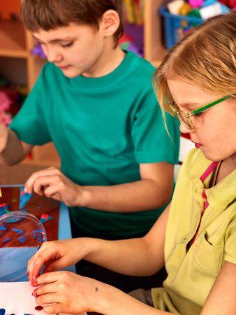 Children model from plasticine in school craft lesson. Arts and crafts group kids in preschooler. 版權商用圖片