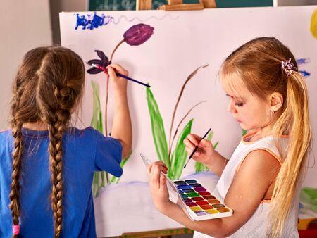 Children paint on an easel by watercolor in preschool classroom.