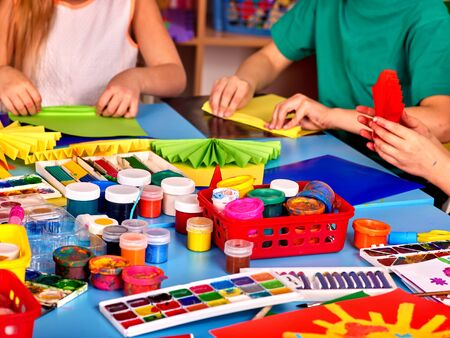 Children are engaged in origami and paint pictures in art school.