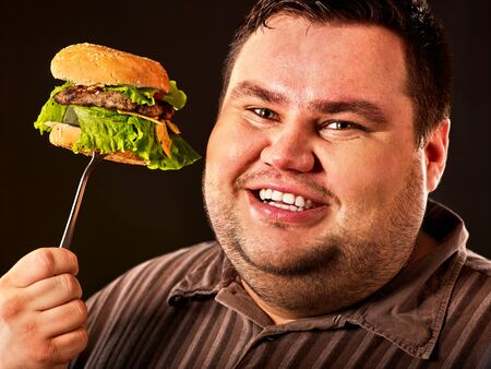 Fat man face eats burger on fork. Obeseness and overnutrition of fast food hamburger concept. 版權商用圖片