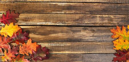 Autumn maple leaves on top view wooden table. Horizontal frame with corner