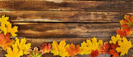Autumn maple leaves on top view wooden table. Horizontal frame with foliage on bottom edge