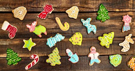 Decorative Christmas cookies background on wooden board. A lot of ginger biscuits Xmas tree and gingerbread man and other cookie cutters with icing on horizontal frame. 版權商用圖片