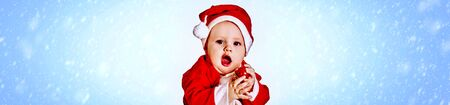 Baby boy in Santa Claus costume into horizontal long frame and blue snowflake background. Standard-Bild