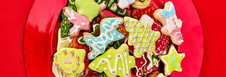 Christmas gingerbread cookies on red Xmas plate and same color background . Top view horizontal long frame design frame.