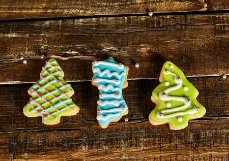 Decorative Christmas cookies sparse on wooden board table. Top view of three horizontal ginger biscuits Xmas tree with icing on square frame.