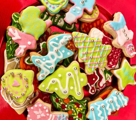 Christmas gingerbread cookies on red Xmas plate and same color background . Close up top view square design frame.