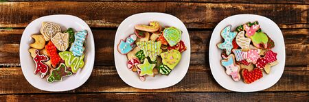 Christmas gingerbread cookies on three plates banner by wooden table. Top view long horizontal banner design frame.