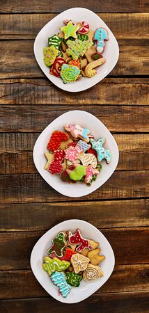 Christmas gingerbread cookies on three plates by wooden table . Top view long vertical banner design frame.