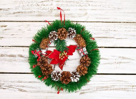 Christmas wreath decoration hangs on front door who made from white wooden boards.